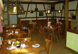 Gastraum der gemütlichen Gaststube mit typisch thüringerischen Kachelofen